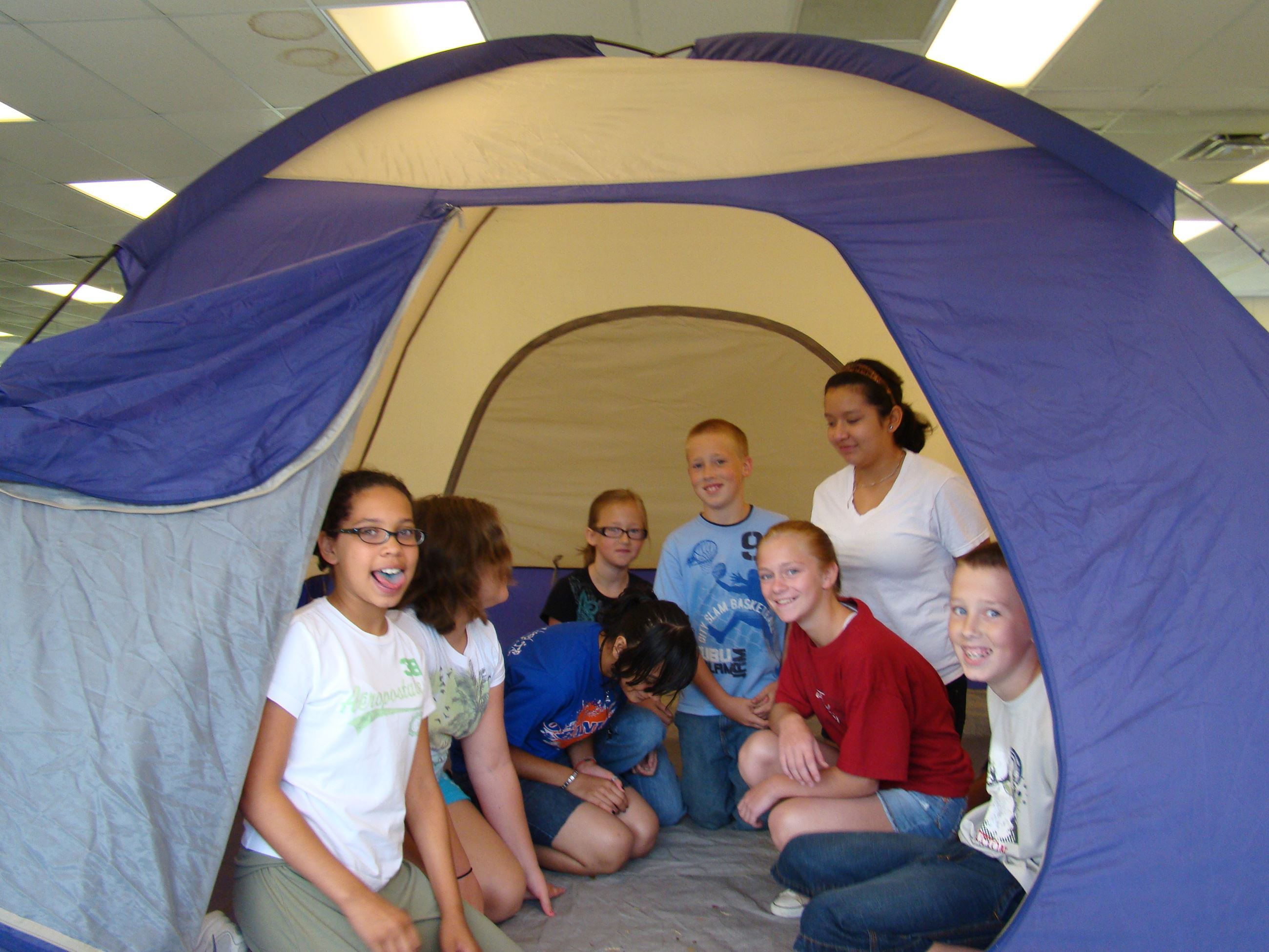 Kids in a tent during camp activities.