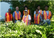 Seven Volunteers Standing and Wearing Orange Vests
